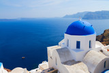 traditional blue dome of church and blue sea water, Oia, Santorini island, Greece