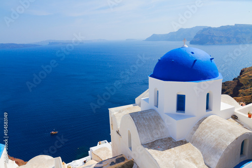 Staande foto Santorini traditional blue dome of church and blue sea water, Oia, Santorini island, Greece