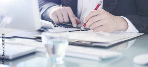 Leinwandbild Motiv Lichtstimmung Geschäftsmann kalkuliert mit Taschenrechner