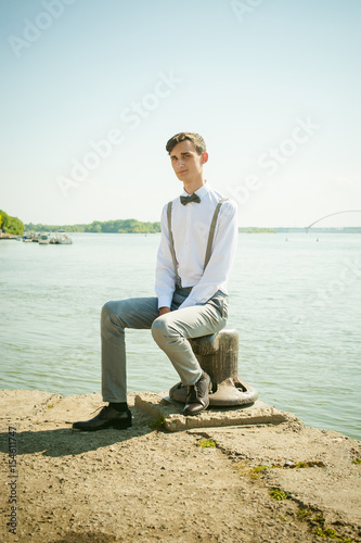 young skinny man, elegantly stylishly dressed in white shirt, gray trousers with suspenders and bow tie. guy sitting on a pier in the background of the river