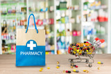 Recycled paper bag with a blue Pharmacy logo on a drugstore counter with pharmacy background shelf blurred blur focus drug medical shop drugstore medication background
