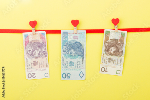 Poster Fifty, twenty, ten zloty hangs on the clothespins, yellow background