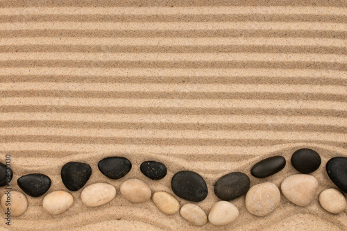 Foto op Plexiglas Stenen in het Zand Two rows of stones, black and white lying on the striped sand, with space for text.