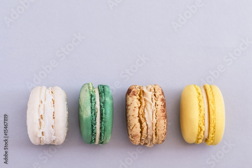Row of colorful french macaroons on gray background Poster