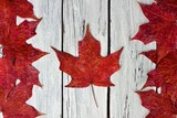 Canadian flag made of red maple leaves over a weathered white wood background