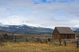 Abandoned Ranch Against Snow Covered Mountain Backdrop - 154693125