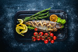 Trout fish baked with aromatic herbs and spices. On Wooden background. - 154738356