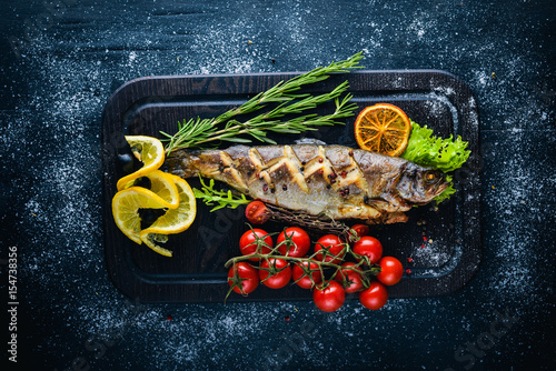 Trout fish baked with aromatic herbs and spices on wooden for Aromatic herb for fish