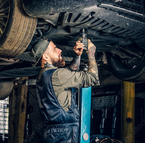 Bearded mechanic working with the car's chassis in a workshop.
