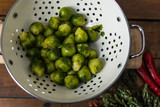 Fresh organic Brussels sprouts in a colander on a wooden background