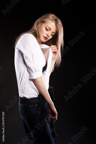 Gorgeous fashionable blonde model with suspenders and white shirt on black background in studio photo