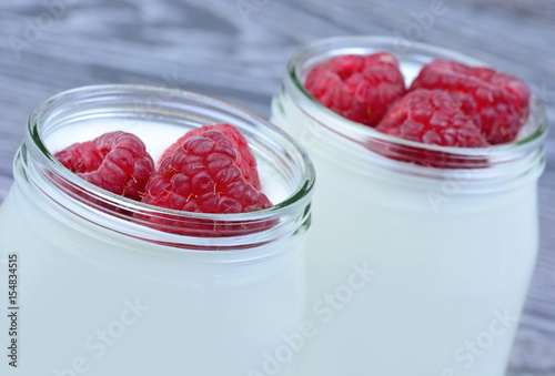 Raspberry with yogurt in a jars on table Poster
