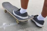 Skater and skateboard legs detail. Lifestyle urban background