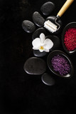Spa Concept. Closeup of beautiful Spa Products with place for text. Bath sea salt with beautiful flower on Spa Hot Stones. Top View.