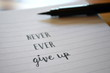 Motivational quote NEVER, EVER GIVE UP hand lettered in notebook
