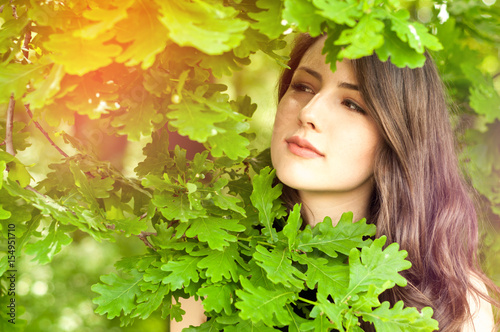 Beautiful woman portrait outdoor standing among tree leaves