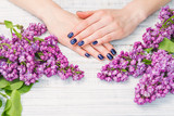 Beauty treatment, woman hands with dark blue manicure and beautiful fresh lilac flowers