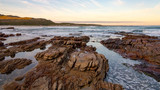 Early morning tide and surf at Scarborough on the Cape Peninsula in South Africa. This photograph is a wide-angle shot of the rocks and surf on a calm morning.