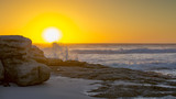 The sun sets behind the spray of a breaking wave at Noordhoek Beach on the Cape Peninsula in South Africa.
