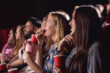 Big group of young best friends, stylish girls and boys watching funny film at cinema, spending free time together, eating tasty popcorn. Pretty and stylish women drinking cola, looking at big screen. - 154984551