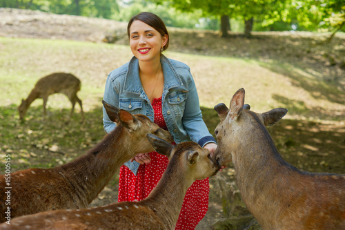 Plakat A young woman and deers outdoors