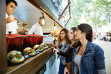 Three beautiful young women buying meatballs on a food truck. - 155075355