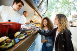 Two beautiful young women buying meatballs on a food truck. - 155075376