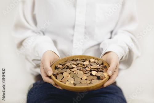 Poster Frau hält bettelnd Schüssel aus Holz mit Geldstücken in den Händen