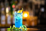 Closeup glass of blue lagoon cocktail decorated with lime at festive bar counter background. - 155106185