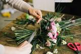 Девушка флорист собирает красивый букет girl florist makes a beautiful bouquet - 155108502
