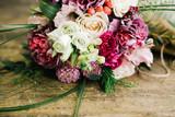 Bouquet of flowers on a wooden table Букет цветов лежит на деревянном столе - 155108750