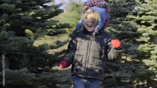 Cute Little Boy Runs Between Christmas Trees, With Big Smile