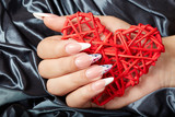 Hand with long artificial french manicured nails holding a heart