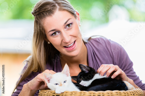 Poster Portrait of happy young woman stroking cute kittens in basket looking in camera
