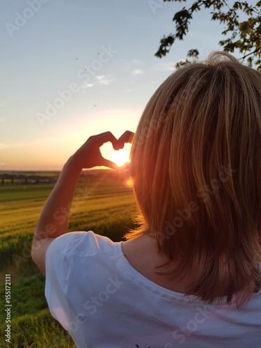 Mädchen formt Herz mit den Händen im Sonnenuntergang