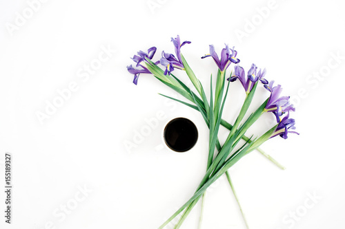 Aluminium Iris Cup of coffee and purple iris flowers on white background. Flat lay, top view.