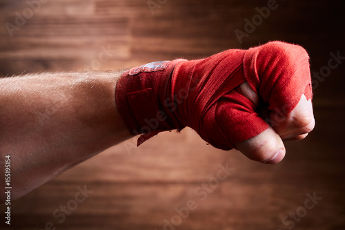 Póster Close up image of fist of a boxer with red bandage against brown background