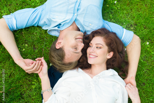 Happy couple relaxing on the grass Poster