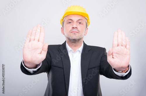 Attractive contractor wearing helmet gesturing stop