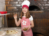 little girl cook putting olives on pizza