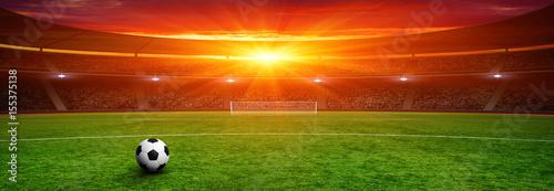 Fototapeta Soccer ball on green stadium