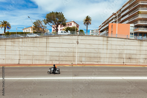Plakat Photo of the motorcyclists passing street in Cannes.