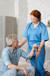 Graceful qualified doctor happy assisting her mature patient