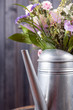 vertical still life flowers in watering can dark background - 155444944