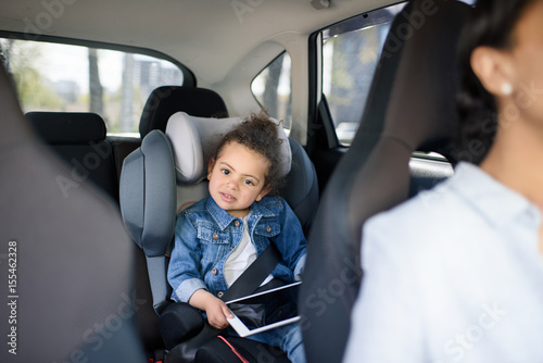 little girl holding digital tablet while sitting in car