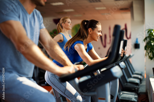 Poster Young woman and man warming up on bikes in the gym