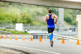 male runner in compression socks running in road with traffic cones safety