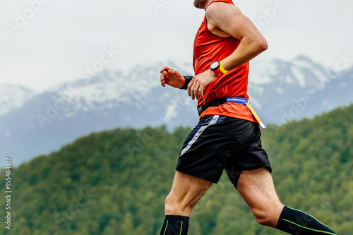 running athletic male with watch on hand on background mountains and green forest
