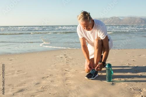 Poster Senior man tying shoelace at beach