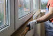 Worker is installing a window sill.